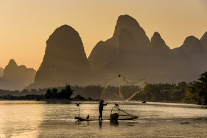 Cormorant Fisherman casting his net on Li River, Xingping, Photo Tour China