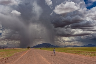 Photographer in dramatic landscape Namibia. Namibia photo tours