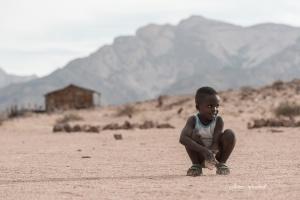 Damaraland boy with village background Namibia Photo Tour